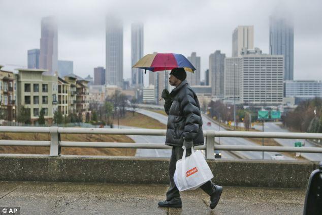 Gray skies: Bernard Mansi walks along the Jackson Street bridge against a rainy Atlanta skyline