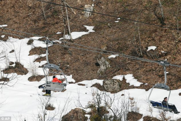 Where did it go? People take a ski lift past patches of snow at the Sochi Olympics on Tuesday as officials revealed they had to take back-up snow out of storage to fill in parts of courses that needed it