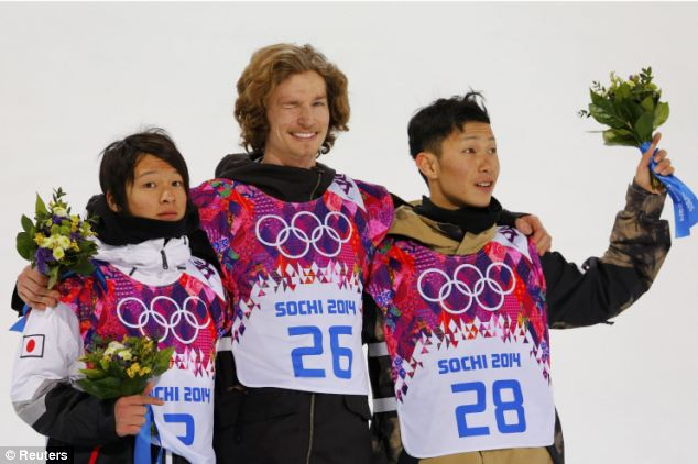 Joy: He stands beside silver medalist Ayumu Hirano, left, and bronze medalist Taku Hiraoka both of Japan
