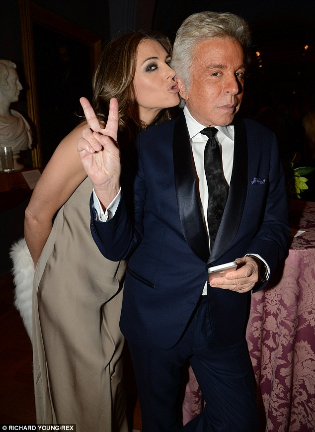 Sealed with a kiss: Liz puckered up to Valentino president Giancarlo Giammetti inside the glittering black tie event