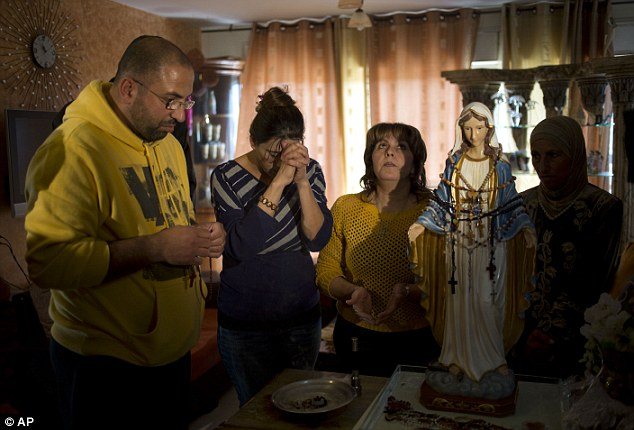 Homage: Worshipers pray next to a the Virgin Mary statue in Tarshiha, a small town in northern Israel