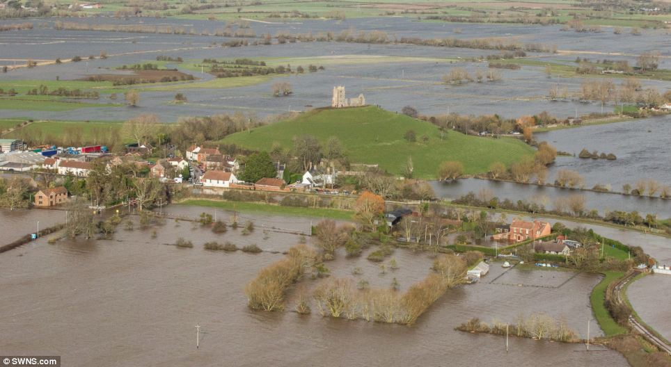 Under water: Burrow Mump has been steeped in water - with only hills, a few homes and a castle visible