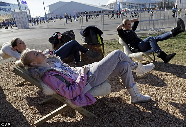 Kicking back: Women relax on deck chairs as warm weather gives a milder feel to the Olympic Park