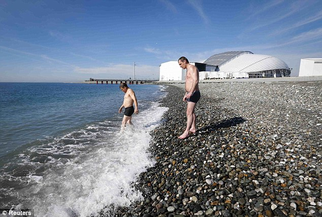 A new Olympic sport: Men wade tentatively into the sea with the main Games stadium visible behind them