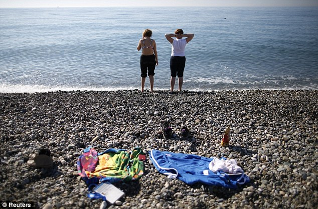 Lovely day for some skiing: Two Winter Olympics volunteers disrobed during a break to take a dip