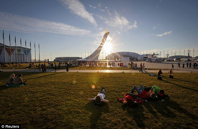 Paradise: Today was a beautiful day in Sochi - but not for athletes, who struggled to cope with the warm weather as it melted ski and snowboard runs. Pictured is the sun setting over the Olympic cauldron
