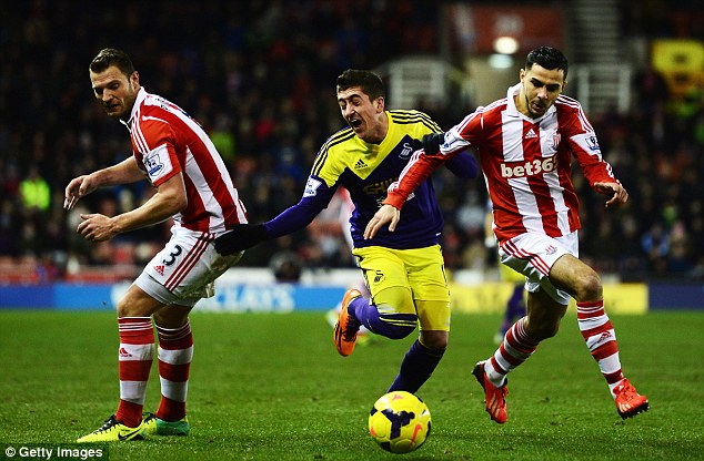 Caught in the middle: Swansea wideman Pablo Hernandez (centre) is crowded out by Erik Pieters and Oussama Assaidi