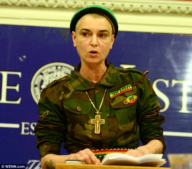 Listen up: The singer dressed in an unusual army uniform complete with a big crucifix necklace for a debate