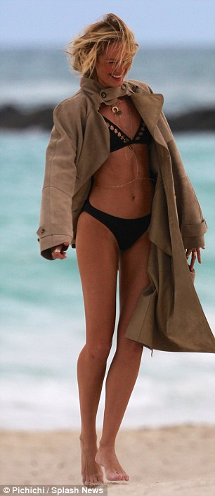 Well it is cold! Rather unusually, Candice wore a camel-coloured coat over the bikini, clasping it closed at the neck while keeping the rest unbuttoned