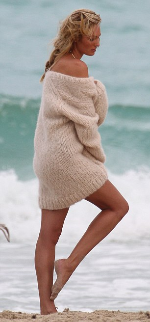 It's cold out here: The model wrapped up in the chunky sweater as she posed at the water's edge