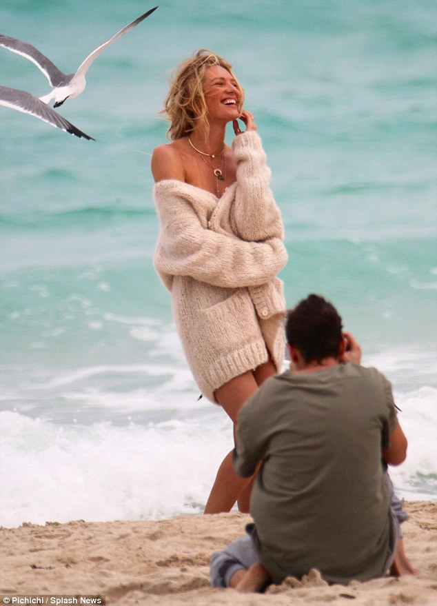 Million dollar smile: Candice grinned as she posed for the camera, the sweater falling alluringly around her shoulders