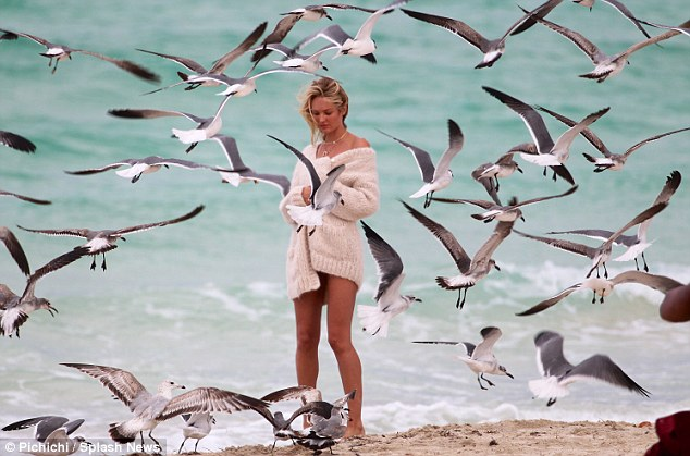 Poetic: The stunner was later seen wearing a cosy oversize cream sweater worn over another black bikini as a flock seagulls surrounded her