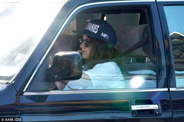 Cruising: Kristen Stewart went incognito under a giant baseball cap and black sunglasses as she drove around LA on Wednesday