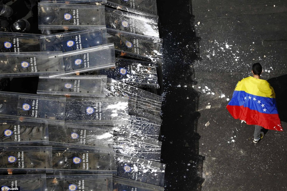 Taking sides: A man with a Venezuelan flag draped around his shoulders walks defiantly in front of riot police, which were forced to create a 'shield wall' after anti-government protesters began throwing items at them