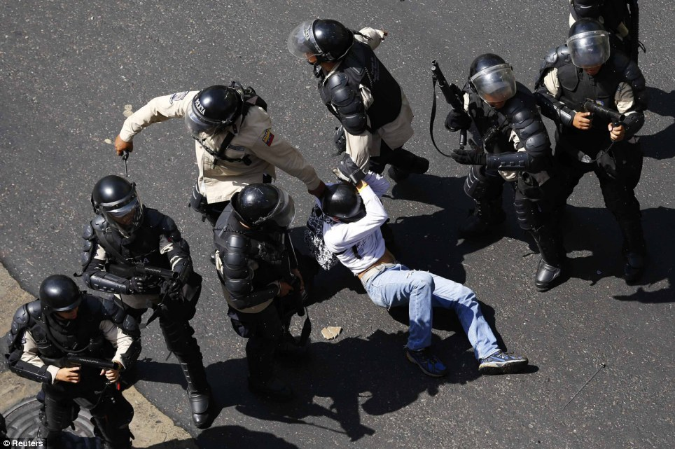 Bad choice: The young man was immediately detained after jumping over the riot police line as the protest escalated into the worst bout of unrest in Venezuela since protests against President Nicolas Maduro's April 2013 election began