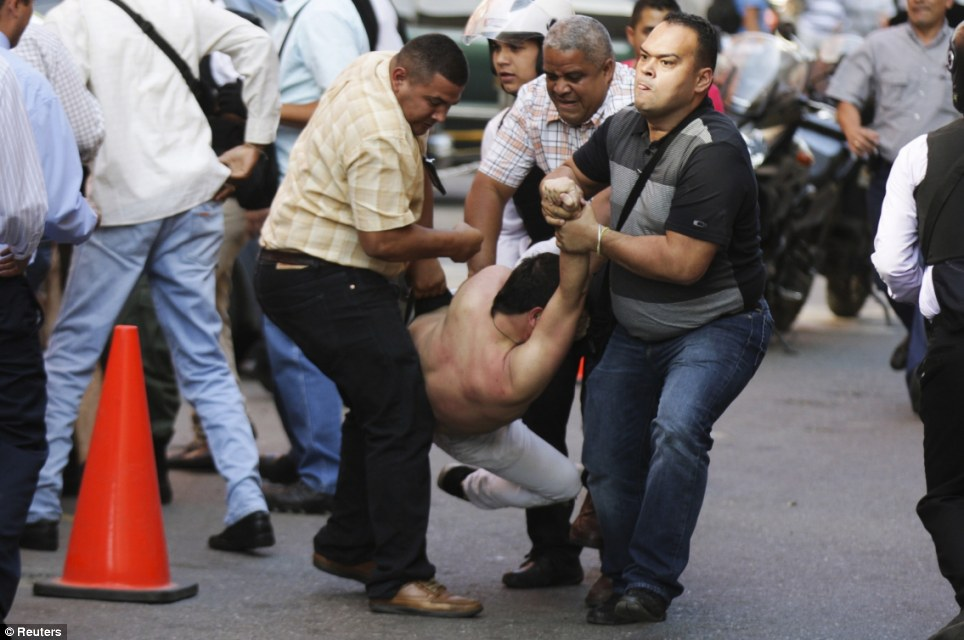 Hiding in plain sight: A demonstrator is detained by plainclothes policemen during the standoff which turned into the most violent protest since Maduro's 2013 election win