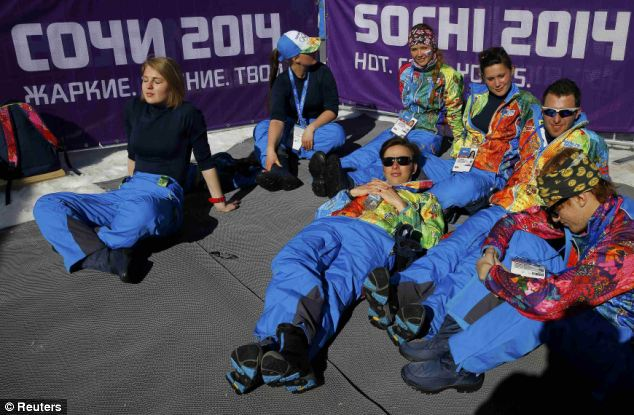 Lying down on the job: The women's 10km cross-country classic was particularly bathed in sunshine. For some volunteers, it all appeared a bit too much