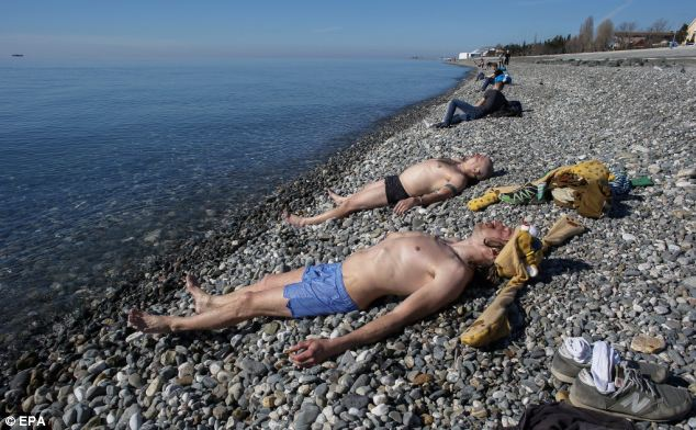 Russian men relax in the sun after swimming in the Black Sea near the Fisht Olympic Stadium on February 13