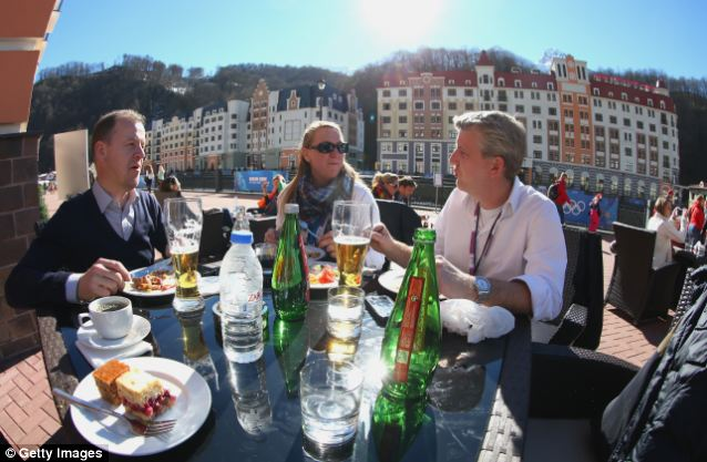 Unexpected bonus: Visitors enjoy the sun over lunch on day six of the Winter Olympics