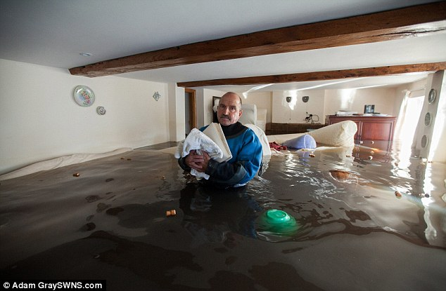 Mark Corthine clutches onto his wedding photograph album as he returns to his home wearing a dry suit in the flooded abandoned village of Fordgate, Somerset, to collect some prized possessions