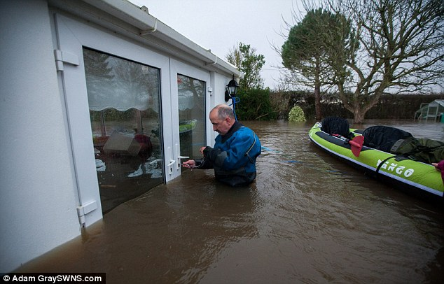 Mark Corthine locks his door after returning to his home wearing a dry suit in the flooded abandoned home