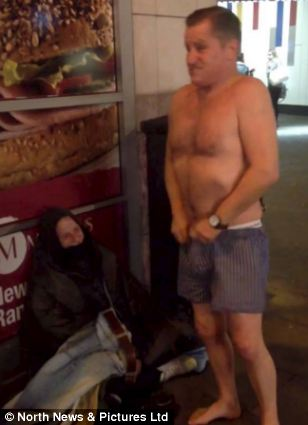 Edward removes his boxer shorts and hands them to the stunned beggar
