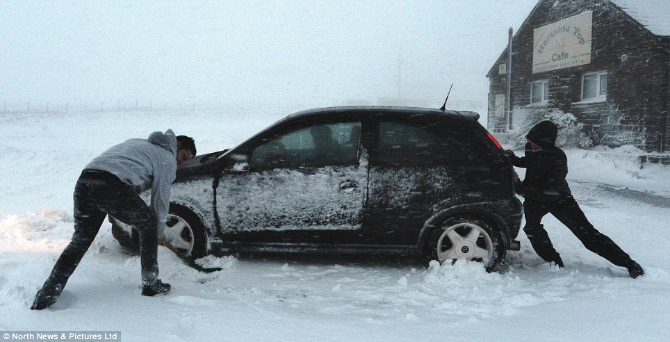 Extreme: A motorist is helped by two passengers after getting stuck in snow in Hartside, Cumbria yesterday