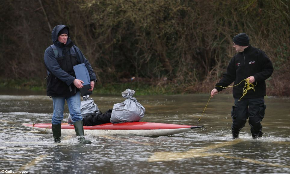 Residents pull their possessions in a canoe on a flooded street near Staines-Upon-Thames. Homes and businesses across the country have suffered severe damage from the relentless storm