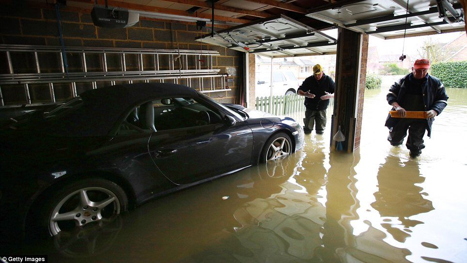 Trouble: Alan Hayward, left, and Jeff Anderson, right, try to recover Mr Anderson' Porsche from his garage in Staines