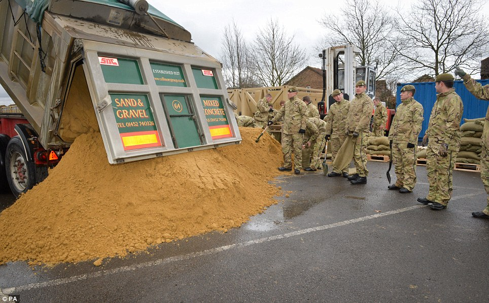 Supplies: Soldiers from the 2nd Battalion, The Royal Welsh, empty a truck ready to fill sandbags in Gloucester