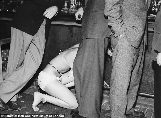 A female entertainer in bikini looks for something on the floor amongst the feet of men standing at the bar in a night club, c.1955