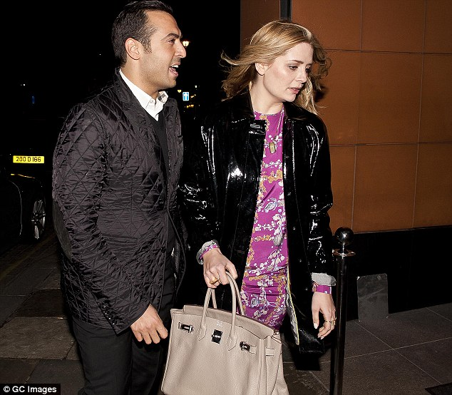 Keeping close: Mohammed walked close behind his dinner companion, wearing a black quilted jacket and trousers