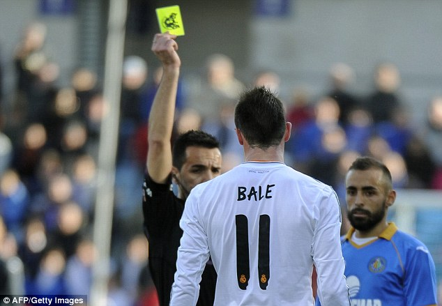 Getting used to it: Gareth Bale had a frustrating afternoon, setting up the first but also getting booked (below)