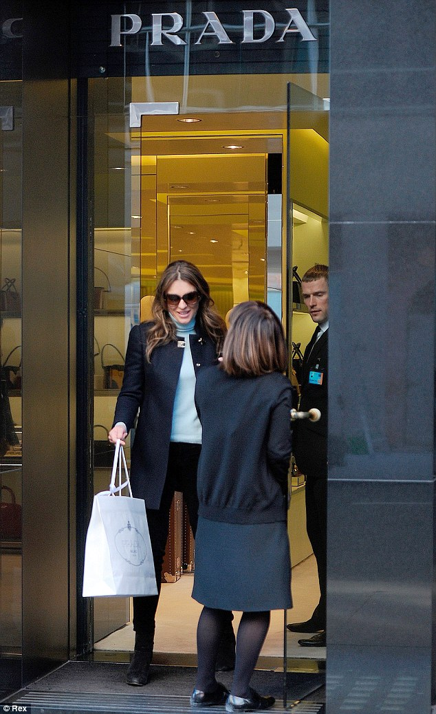 Lucky lady: Liz looked really happy as she left a Prada store in London on Thursday clutching a shopping bag