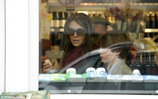 Off-duty: The brunette beauty kept her sunglasses on while in the store after wrapping up in a purple scarf