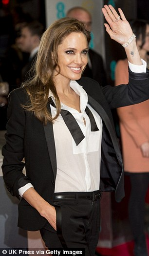 Happy lady: The 38-year-old showed off her fabulous figure as she wore her tie undone over a sheer tuxedo shirt