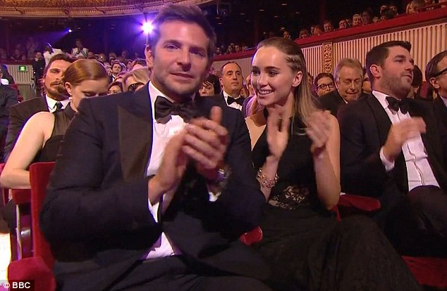 Taking it in: Suki took pride of place next to Bradley, while his American co-stars Amy Adams and Christian Bale could be seen sitting in the rows behind