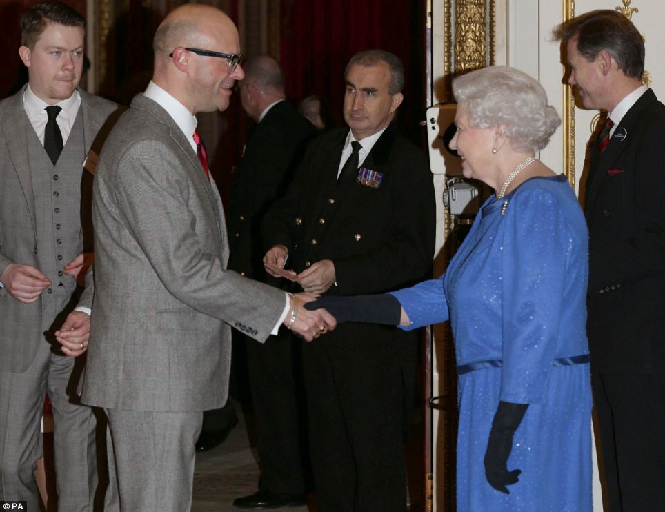 Looking jolly: Her Majesty greets award-winning comedian Harry Hill, who was wearing a grey suit and red tie