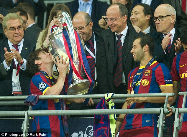 Triumph: Lionel Messi kisses the Champions League trophy back in 2011 as Javier Mascherano looks on