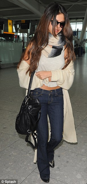 Big night? Selena kept her shades on as she made her way through the airport allowing her hair to fall across her face