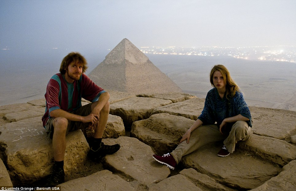 Risky: Ms Grange and her friend Max sit on top of the Great Pyramid of Giza which they scaled under the cover of darkness despite armed security patrolling the area