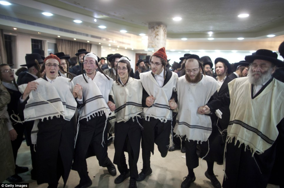 Keeping with the traditions: Only men can be seen dancing in this picture as the women have their own celebrations on the other side of the lace veil