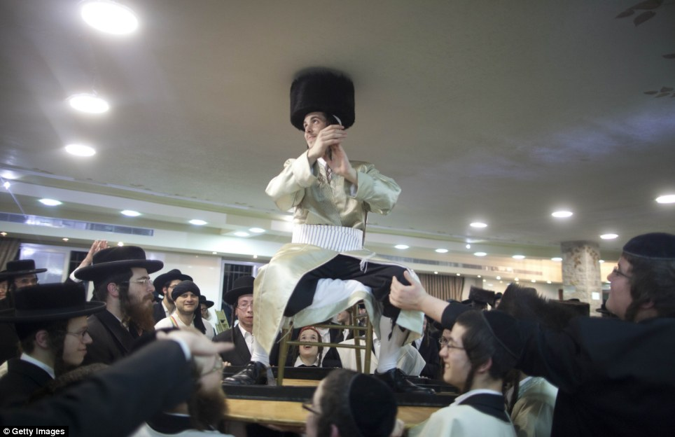 Musical traditions: The male guests performs customary horah - a circle dance -  during which Aharon is raised in the center on a chair put on an upside down table