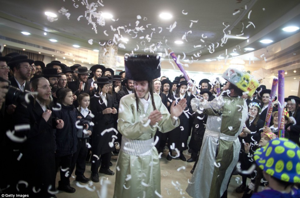 Day of joy: Men, young and old, dance along with the groom Aharon Cruise on his wedding day, while the women celebrate separately, on the other side of the white veil seen in the far background