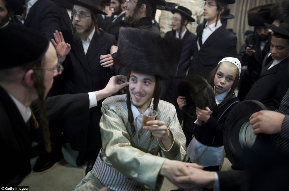Groom Aharon is cheered on and toasted by male friends and relatives, while his bride celebrates separately