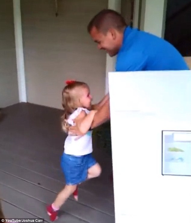 Reunited: The toddler takes several minutes to remove all the wrapping paper. When she finally opens the flaps, her father pops out, and Bridget screams, laughs and jumps into his arms