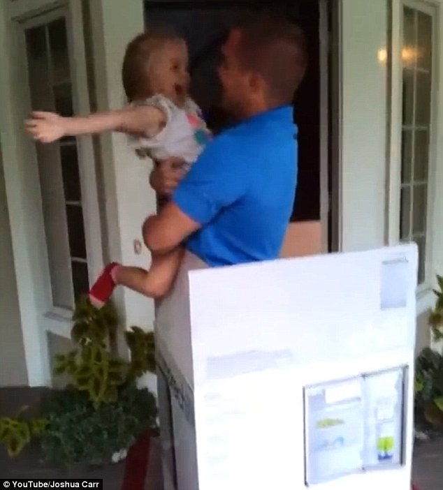 Overjoyed: Her dad lifts her into his arms as she squeals and giggles