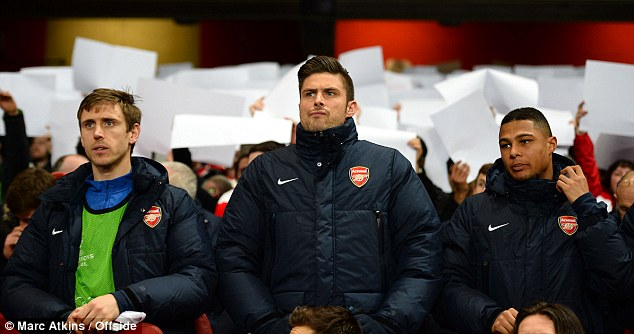Difficult week: Giroud, who has endured a personal crisis after he was pictured this week in a hotel room with a lingerie model, did not look happy to be sitting on the bench among the Arsenal substitutes