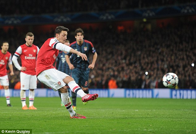 Hit and hope: Ozil picked himself up off the floor and struck his penalty towards goal with his left foot