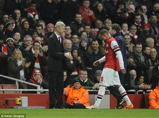 Crocked: Kieran Gibbs (centre) trudges off past boss Arsene Wenger with a suspected hamstring injury